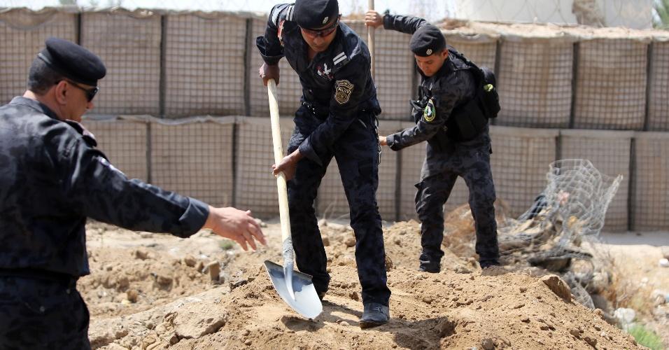 13.jun.2014 - Policiais iraquianos cavam trincheiras no posto de controle na cidade de Taji, na entrada de Bagdá, enquanto as forças de segurança estão reforçando as defesas na capital