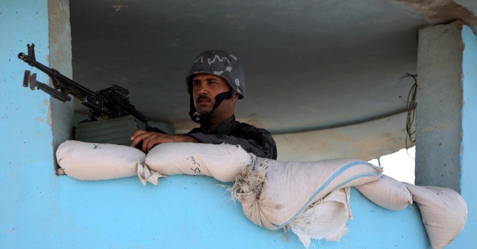 13.jun.2014 - Policial iraquiano monta guarda em um posto de controle na cidade de Taji, nos arredores de Bagdá, enquanto as forças de segurança estão reforçando as defesas na capital