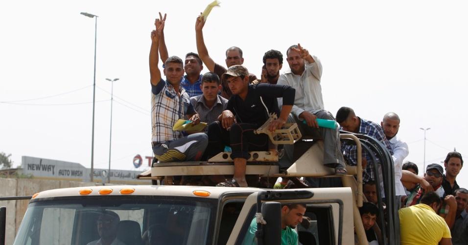 13.jun.2014 - Voluntários, que se juntaram ao Exército iraquiano para combater os insurgentes islamitas, viajam em um caminhão em Bagdá