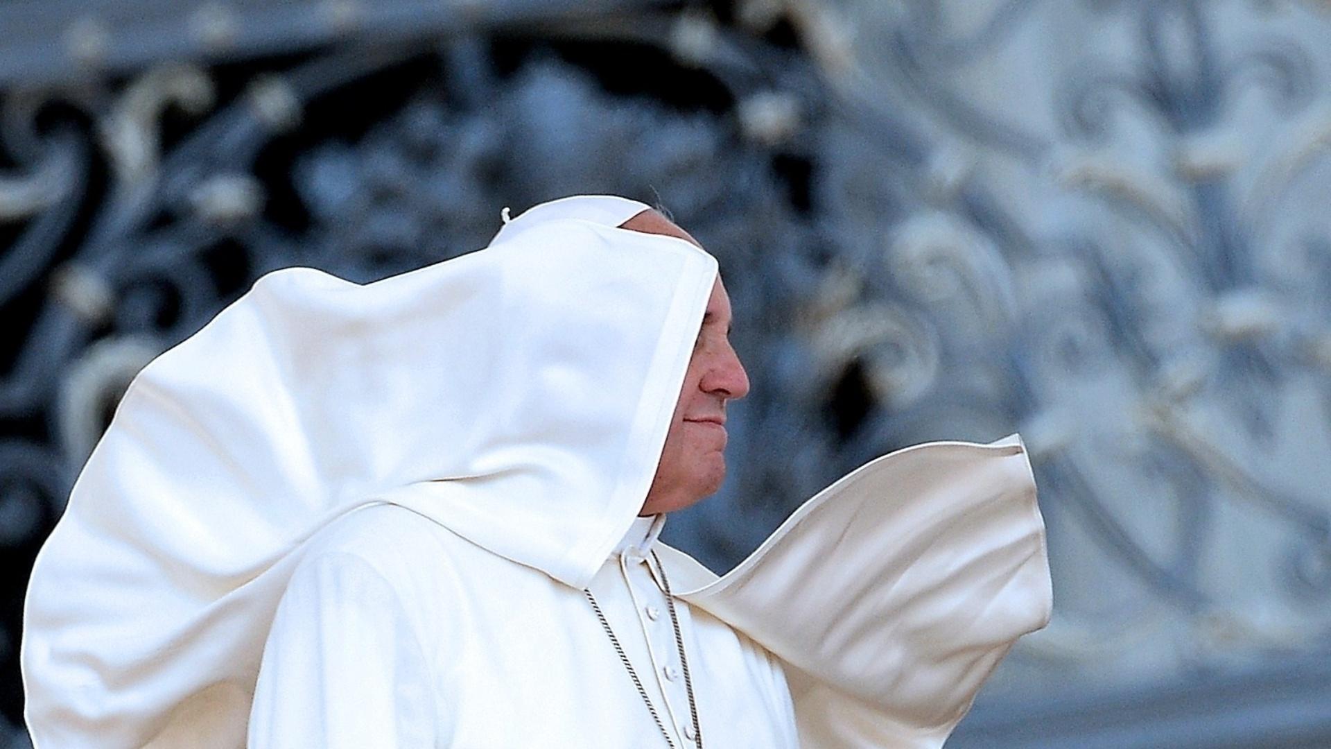14.jun.2014 - O vento fez parte da roupa do papa Francisco cobrir seu rosto quando ele olhava para a Praça de São Pedro, no Vaticano, durante uma audiência com voluntários católicos. O papa reuniu-se, neste sábado (14), com integrantes da Confederação Nacional da Misericórdia da Itália