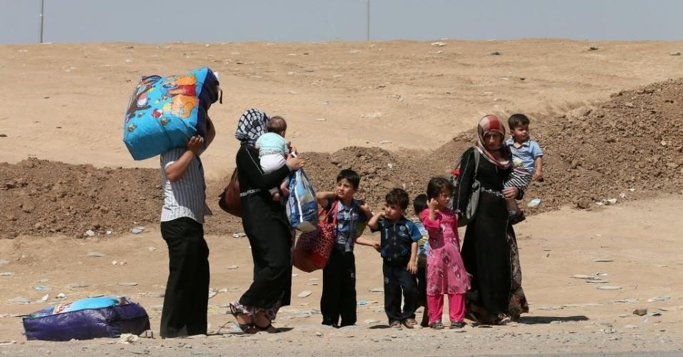 16.jun.2014 - Refugiados iraquianos, que fugiram da violência causada por milícias jihadistas na provícia de Nineveh, carregam pertences ao chegarem a al-Hamdaniyah, na região da província autônoma curda. Os insurgentes sunitas do Estado Islâmico do Iraque e do Levante (EIIL) assumiram o controle de mais uma cidade no noroeste do Iraque de maioria turcomana, fortalecendo sua presença no norte do país