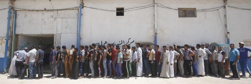16.jun.2014 - Voluntários formam fila para recolher uniformes após discurso do primeiro-ministro iraquiano, Nuri al-Maliki, que anunciou que o governo irá armar e equipar os civis que se voluntariaram para lutar contra militantes jihadistas, na cidade de Karbala