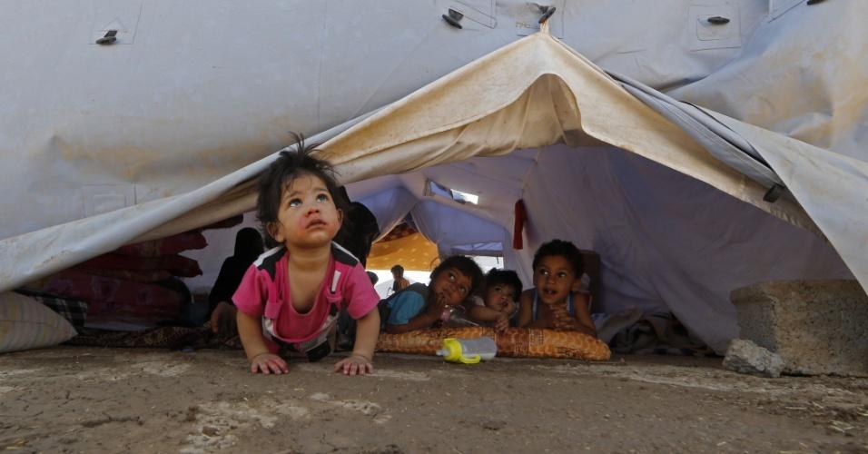 17.jun.2014 - Crianças de abrigam dentro de uma tenda em um acampamento temporário em Aski Kalak (a 40 km da região autônoma curda Arbil). A maior refinaria de petróleo do Iraque, que fica em Baiji (220 km de Bagdá), foi fechada após ser cercada por militantes do grupo jihadista Exército Islâmico do Iraque e do Levante (EIIL), de acordo com informações de autoridades da instalação. Nesta terça-feira (17), estrangeiros foram retirados do local, que continua sob controle do Iraque, e funcionários regionais são mantidos em seus postos
