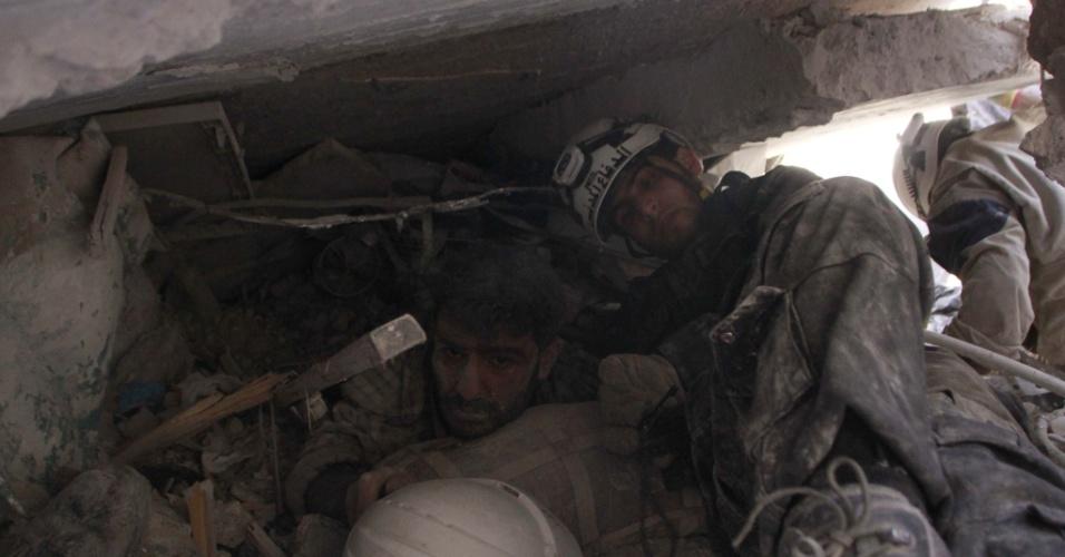 18.jun.2014 - Equipes de resgate retiram um homem de escombros após um ataque aéreo supostamente realizado por forças leais ao ditador sírio Bashar al-Assad, no norte da cidade de Aleppo, na Síria, nesta quarta-feira (18)