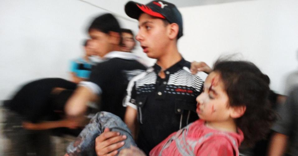 18.jun.2014 - Uma menina ferida é carregada em direção a um hospital após uma ataque aéreo supostamente realizado por forças leais ao ditador sírio Bashar al-Assad, no subúrbio de Saqba, em Damasco, nesta quarta-feira (18)