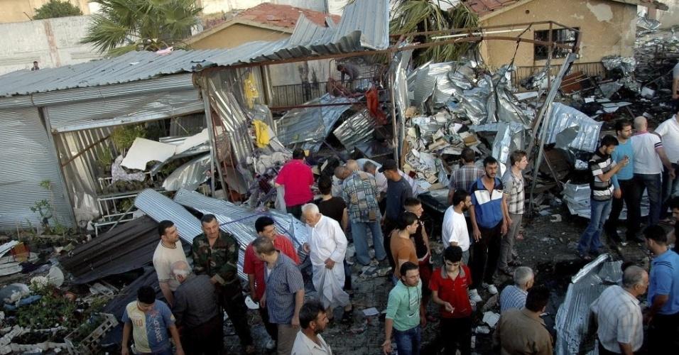 19.jun.2014 - Cidadãos sírios observam os danos causados por um atentado a bomba em Akram, na cidade de Homs, Síria. Seis pessoas morreram e 40 ficaram feridas