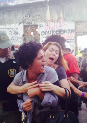 Girlayne Nascimento, 23, grávida de seis meses, é protegida pela advogada Liana Lins durante operação de reintegração de posse do Cais José Estelita, ocupado por um grupo de 100 pessoas desde o mês passado, no Recife (PE), em 17 de junho. A ação foi  condenada pela Anistia Internacional, pelo Ministério Público de Pernambuco e pela Universidade Federal do estado (UFPE)