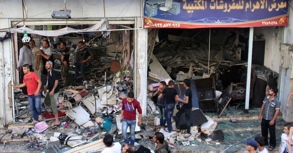 24.jun.2014 - Imagem divulgada pela agência de notícias Sana mostra pessoas inspecionando local onde um carro-bomba explodiu em uma área pró-governo na cidade de Homs, na Síria, nesta terça-feira (24). A explosão feriu 14 pessoas