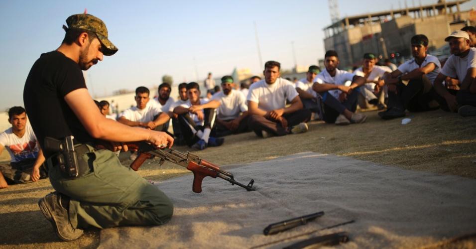 24.jun.2014 - Soldado iraquiano ensina voluntários como montar uma arma. Rebeldes islâmicos vem rapidamente ocupando cidades do país