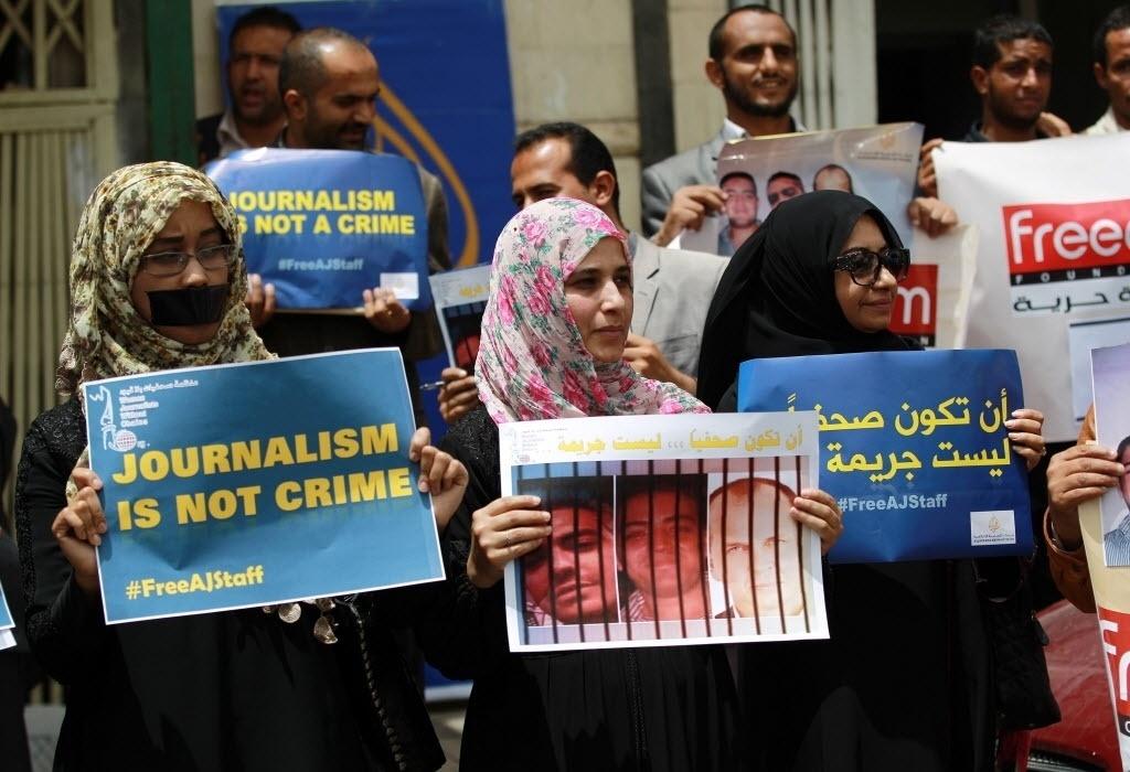 25.jun.2014 - Manifestantes seguram cartazes durante protesto em Sanaa, no Iêmen, contra a prisão de jornalista da Al- Jazeera, no Egito. O presidente egípcio, Abdel Fattah al-Sisi, disse nesta terça-feira (24) que não vai interferir na decisão judicial que condenou os três jornalistas a prisão