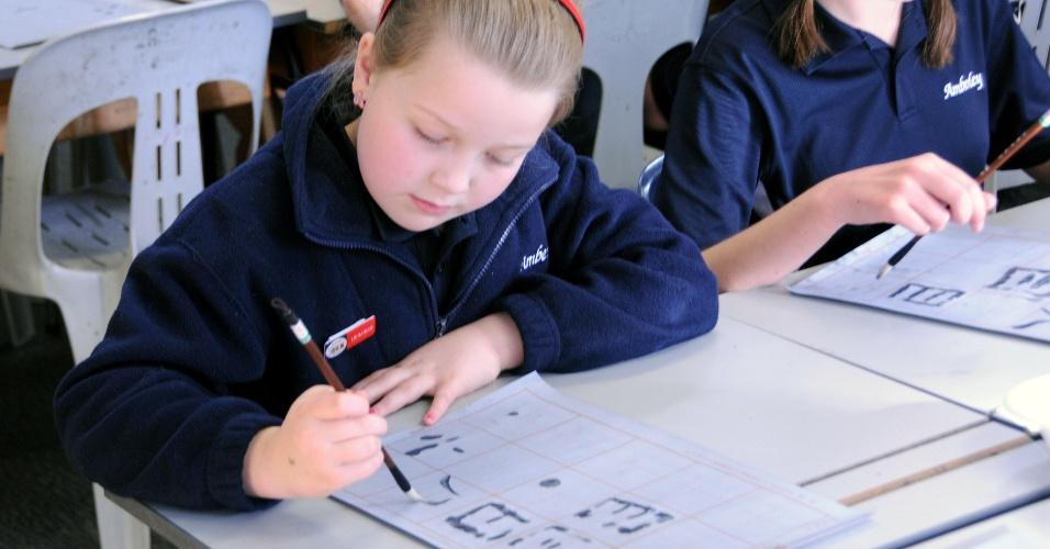 """27.jun.2014 - Estudantes de uma escola em Christchurch, Nova Zelândia, treinam caligrafia chinesa durante o """"Dia da China"""" na cidade"""