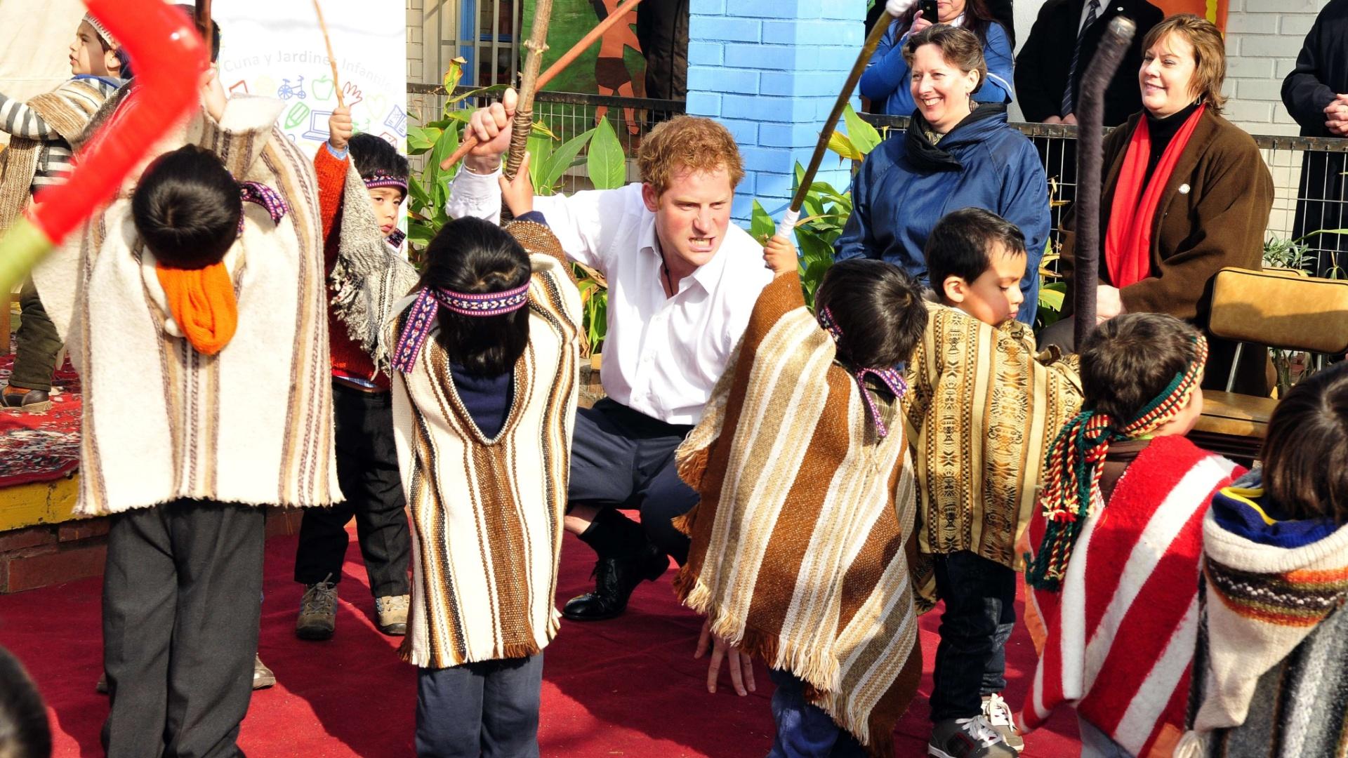 27.jun.2014 - Príncipe Harry brinca com crianças da tribo dos Mapuches, em Santigo, nesta sexta-feira (27