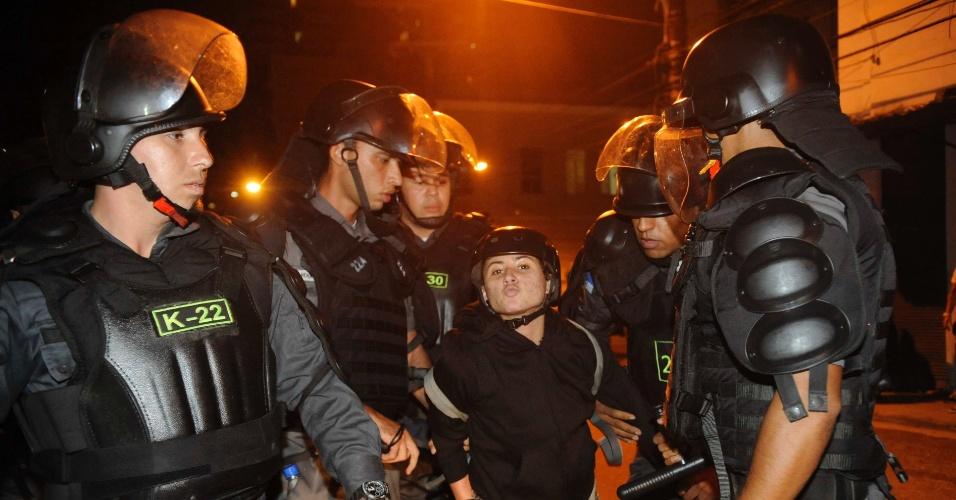 28.jun.2014 - Manifestante solta beijo para câmera enquanto é detida por policiais durante protesto contra a Copa do Mundo, nas proximidades da praça da Saenz Peña, na zona norte do Rio de Janeiro