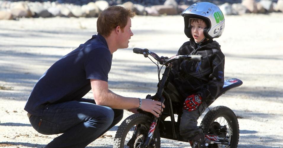 29.jun.2014 - O príncipe Harry, da Inglaterra, conversa com um menino em um local de treinamento de motocross em Antawuay, em Santiago, neste domingo. O nobre termina a sua visita oficial de três dias no país
