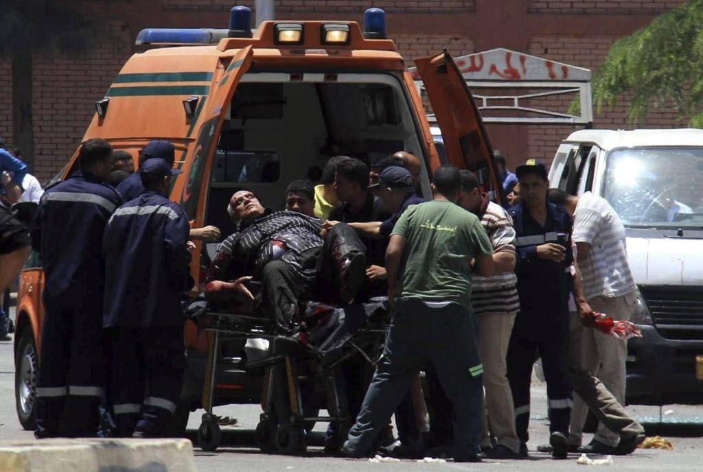 30.jun.2014 - Homem ferido é colocado em ambulância após a explosão de uma bomba diante do palácio presidencial de Al Itihadiya, no leste do Cairo, Egito. Ao menos um policial morreu. A explosão ocorre no dia em que os protestos que levaram à derrubada do ex-presidente Mohammed Mursi, ligado à organização política Irmandade Muçulmana, completam um ano