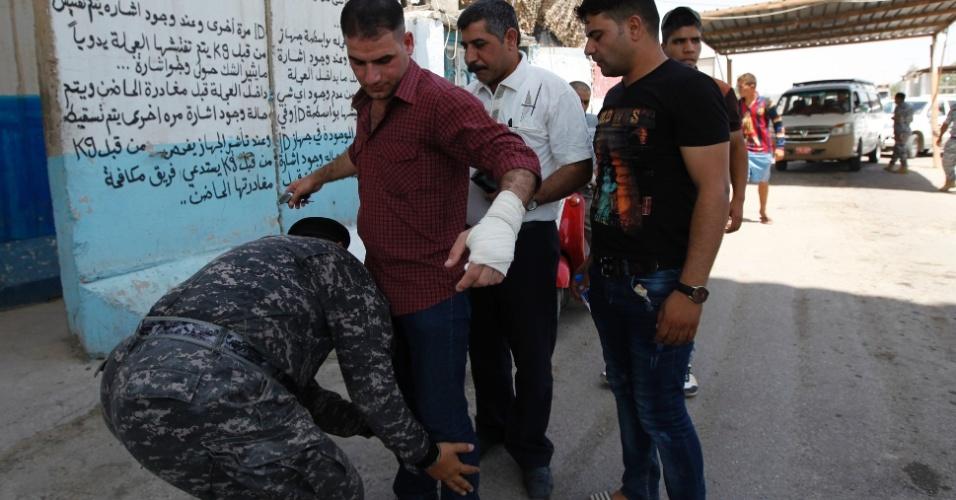 30.jun.2014 - Homens passam por revista em posto de checagem da polícia iraquiana em Bagdá.