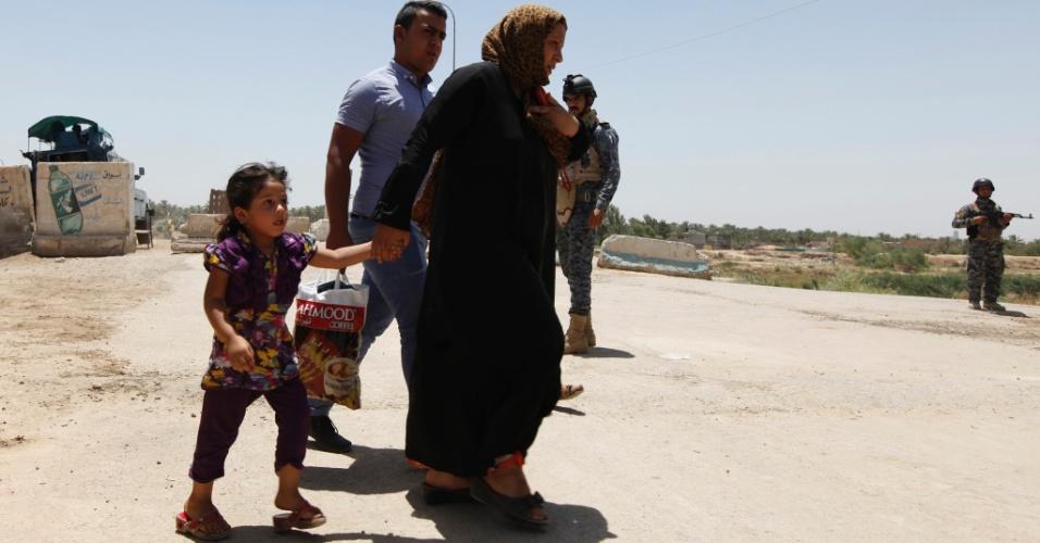 30.jun.2014 - Iraquianos transitam perto de guardas em Bagdá. A segurança foi reforçada na capital iraquiana pois  tropas do país tentam expulsar um grupo de ataque da Al Qaeda. A operação acontece depois de o líder do grupo terrorista ter sido declarado o califa de um novo Estado islâmico em terras confiscadas entre o Iraque e a Síria