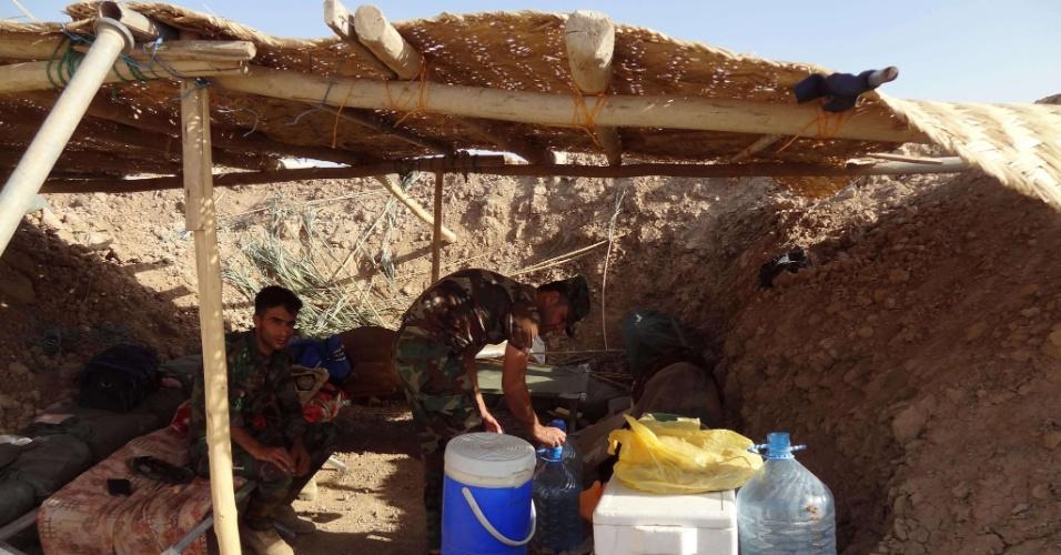 30.jun.2014 - Militares descansam em um posto de controle na estrada que leva ao norte do Iraque. O reforço na segurança foi exigido por causa da ofensiva de militantes sunitas, que se apresentam como herdeiros de um regime que existiu da época do profeta Maomé até um século atrás