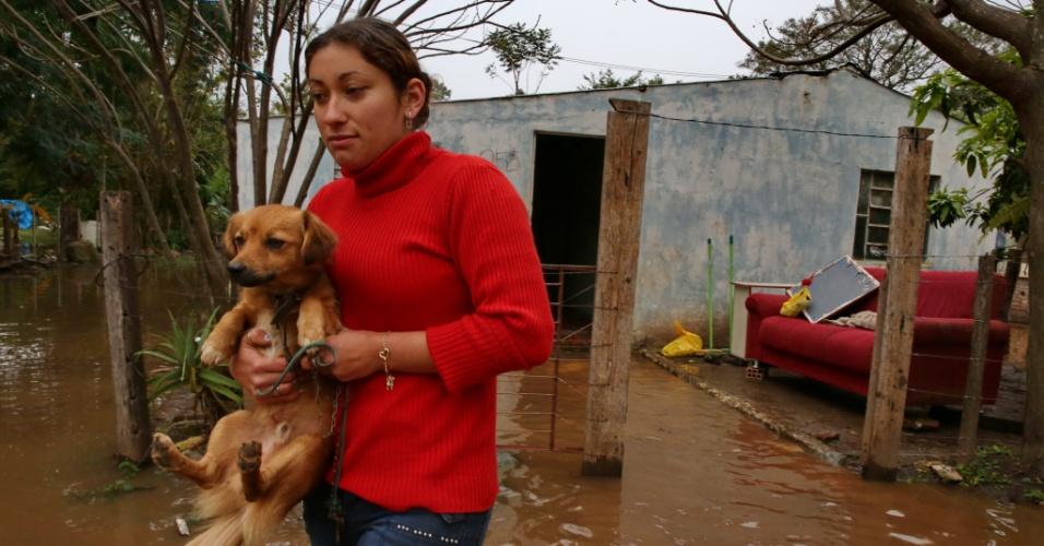 30.jun.2014 - Mulher carrega cachorro em área alagada do município de Itaqui, no Rio Grande do Sul, nesta segunda-feira (30). O número de afetados pelas chuvas no Estado ultrapassou 11,5 mil pessoas. Cerca de 7,6 mil pessoas continuam desabrigadas. A previsão é de que a chuva diminua a partir desta segunda, mas volte na quinta-feira
