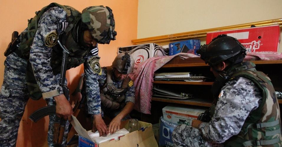 30.jun.2014 - Policiais iraquianos checam caixas em uma casa durante uma operação de busca por armas ilegais.