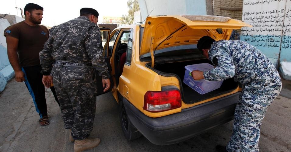 30.jun.2014 - Policiais iraquianos checam o bagageiro de um carro em uma base em Bagdá. Prováveis ataques sunitas de integrantes do Estado Islâmico do Iraque e do Levante (EIIL) motivaram o reforço da segurança na região da capital iraquiana
