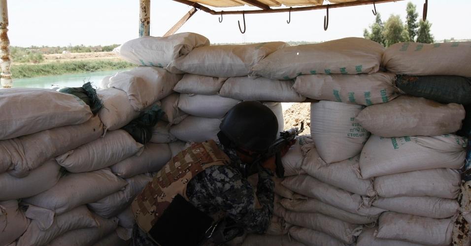 30.jun.2014 - Policial assume posição em área de vigilância em operação para intensificar a segurança no norte de Bagdá