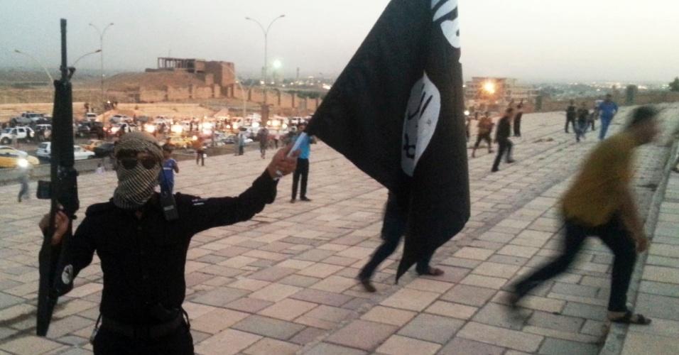 30.jun.2014 - Combatente do Estado Islâmico do Iraque e do Levante (EIIL) foi flagrado agitando uma bandeira do movimento e exibindo uma arma em uma rua de Mosul. O grupo é formado por rebeldes sunitas, que se apresentam como herdeiros de um regime que existiu da época do profeta Maomé até um século atrás