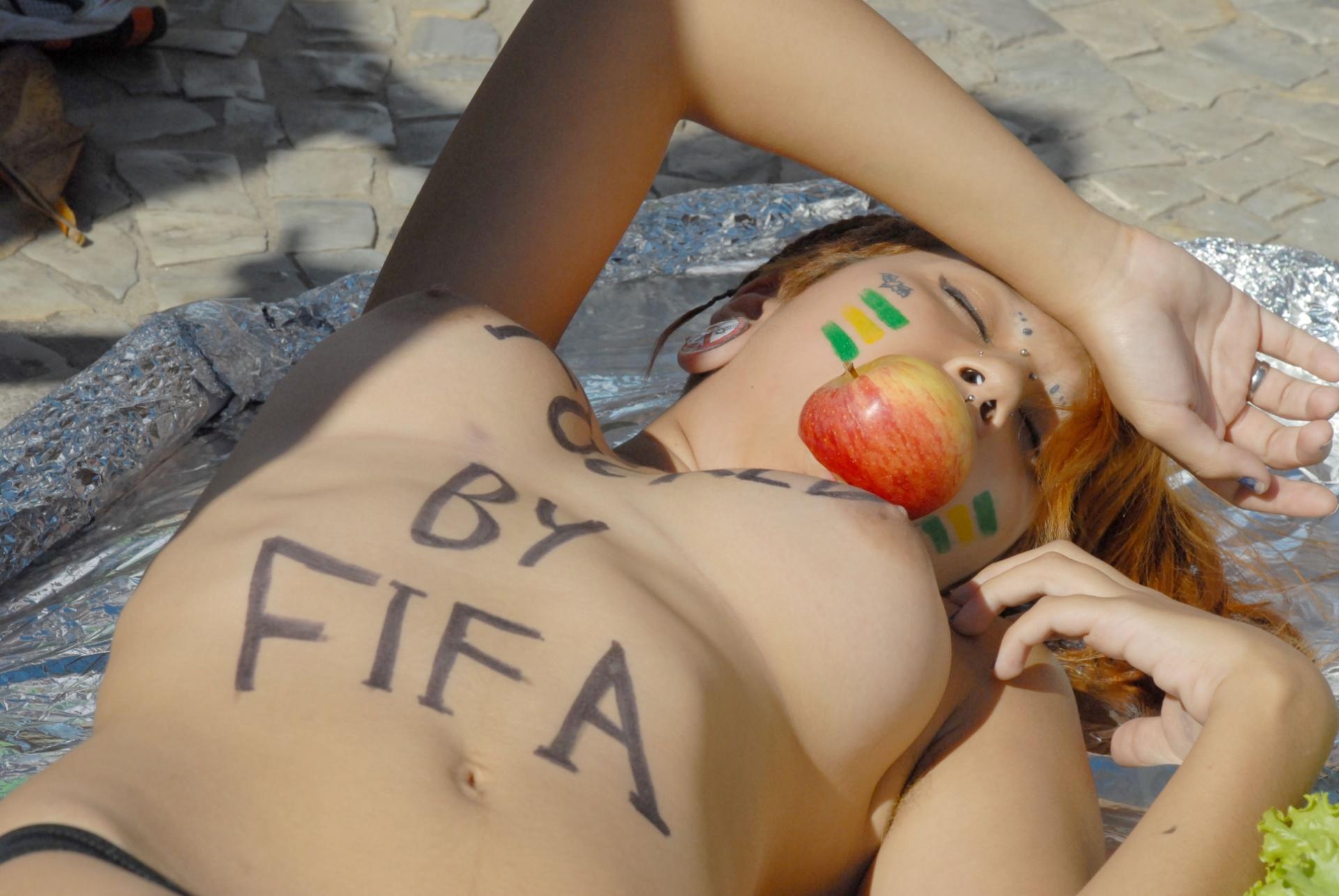 6.jul.2014 - Nua e com uma maçã na boca, uma ativista do movimento Bastardxs, que tem como líder Sara Winter, ex-integrante do Femen, protesta contra o turismo sexual durante a Copa do Mundo, no calçadão da praia de Copacabana, na zona sul do Rio de Janeiro. O ato ocorreu próximo ao local da Fifa Fan Fest