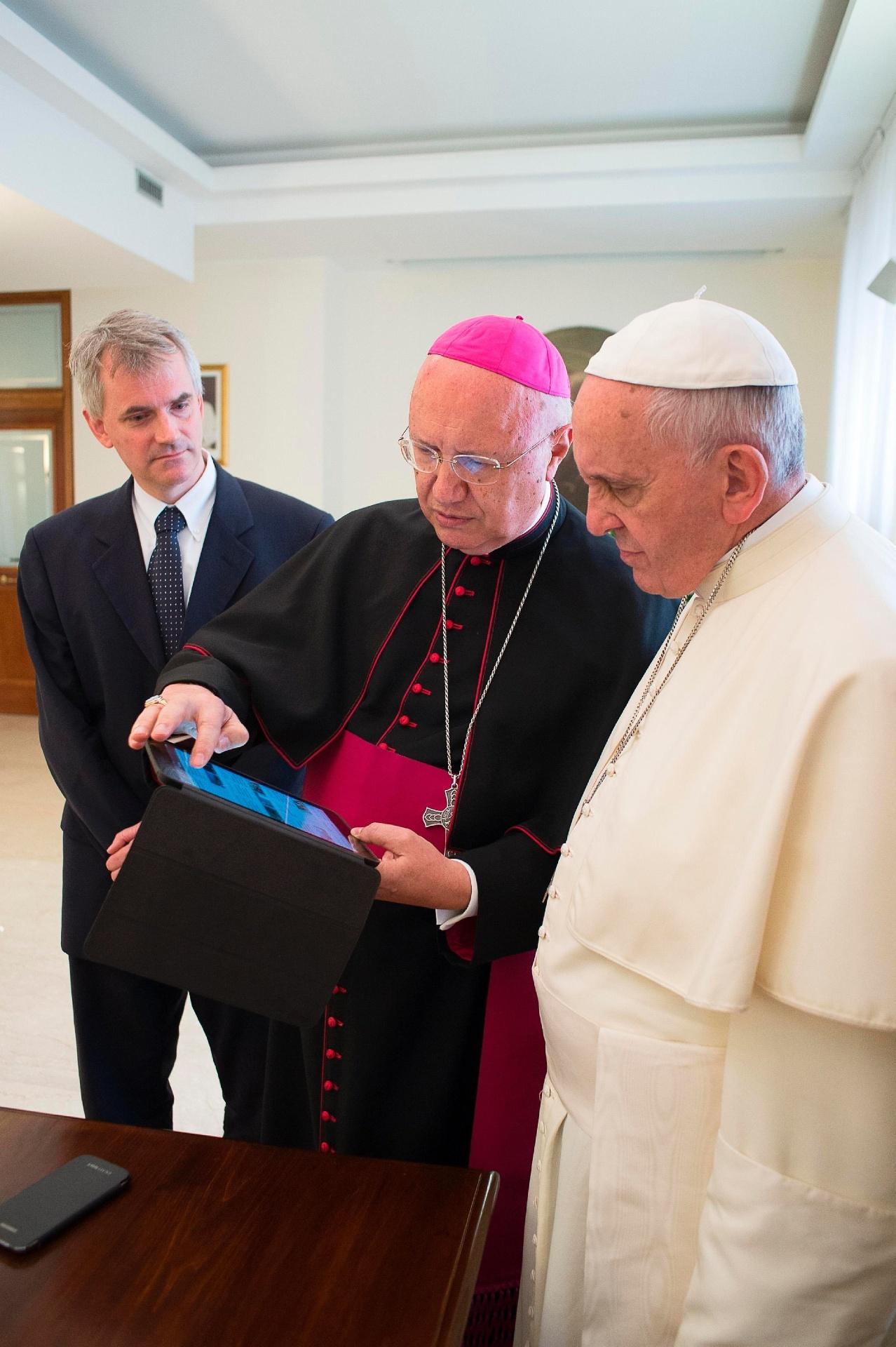 7.jul.2014 - Papa Francisco observa notícia em tablet com o arcebispo Claudio Maria Celli), presidente do Conselho Pontifício para as Comunicações Sociais, durante reunião no Vaticano, nesta segunda-feira (7)