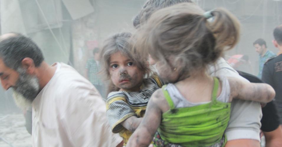9.jul.2014 - Homem sírio carrega duas meninas cobertas de poeira após um ataque aéreo relatado por forças do governo, nesta quarta-feira (9), no norte de Aleppo. De acordo com o Observatório Sírio para os Direitos Humanos, em maio,cerca de 2.000 civis, incluindo 500 crianças, foram mortas nos ataques aéreos ocorridos diariamente