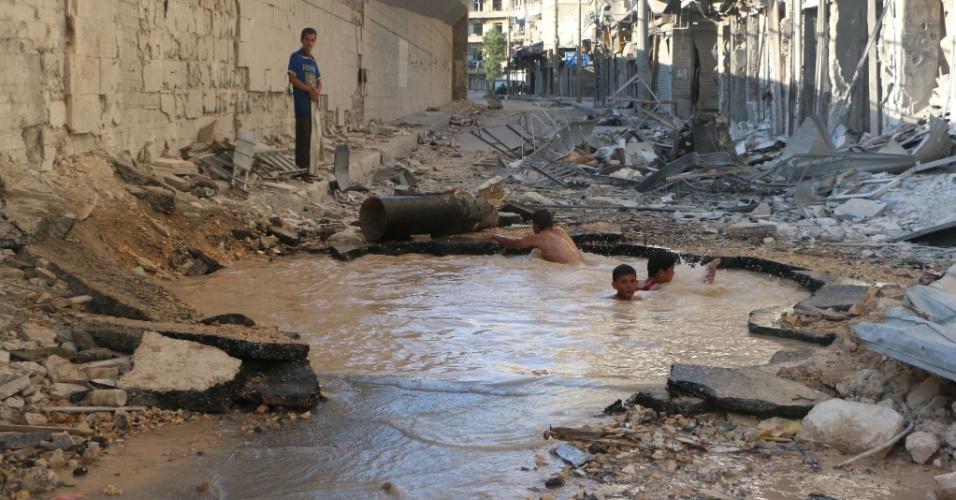 10.jul.2014 - Crianças sírias brincam em uma cratera criada por bomba e cheia de água, nesta quinta-feira (10), no norte de Aleppo