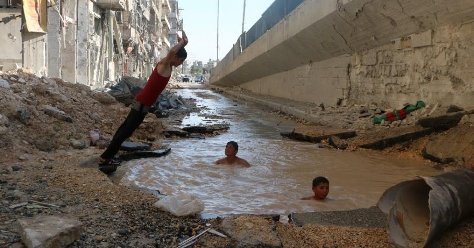 15.jul.2014 - Crianças sírias brincam em uma cratera de bomba inundada com água no norte da cidade de Aleppo, na última quinta-feira (10). Apesar de a água estar suja, as crianças encontram nestas