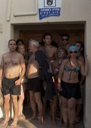 Israelenses e turistas se escondem em banheiro de praia de Tel Aviv durante um ataque de foguete, feito por militantes palestinos da faixa de Gaza