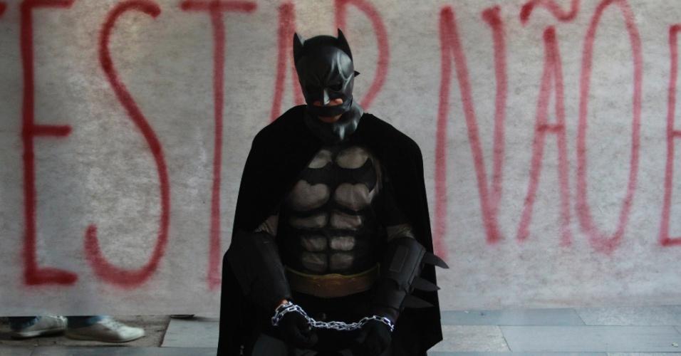 15.jul.2014 - Manifestante vestido de Batman se acorrenta em frente a faixa durante protesto contra a prisão de ativistas envolvidos com manifestações na véspera da final da Copa do Mundo. O protesto acontece em frente ao Tribunal de Justiça do Rio de Janeiro, no centro da capital fluminense, nesta terça-feira (15)