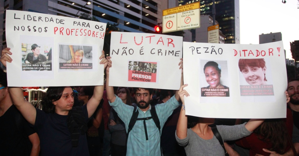 15.jul.2014 - Manifestantes erguem cartazes durante protesto contra a prisão de ativistas envolvidos com manifestações na véspera da final da Copa do Mundo. O protesto acontece em frente ao Tribunal de Justiça do Rio de Janeiro, no centro da capital fluminense, nesta terça-feira (15)