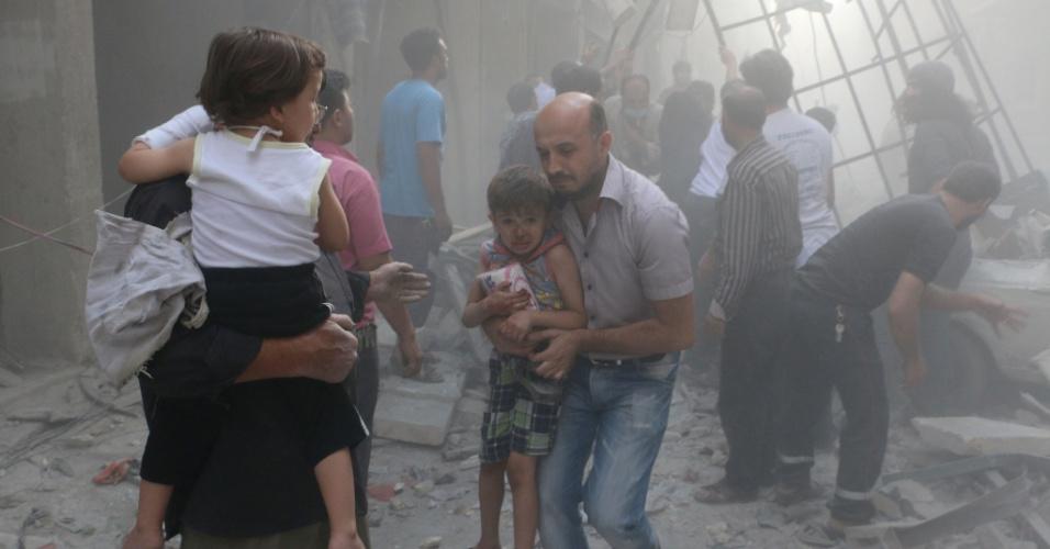 15.jul.2014 - Sírios carregam crianças entre destroços após um ataque aéreo de forças leais ao governo no norte da cidade de Aleppo, na Síria, nesta terça-feira (15). Mais de 170 mil pessoas foram mortas em três anos de guerra civil, um terço delas civis, de acordo com o Observatório Sírio de Direitos Humanos