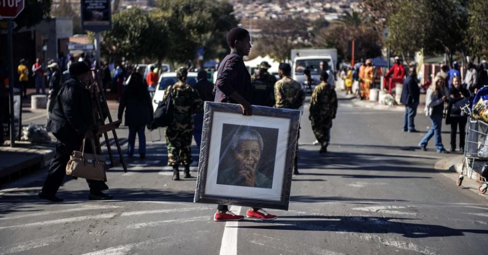 18.jul.2014 - Jovem carrega quadro de Nelson Mandela em frente a casa onde ele morava em Soweto, na África do Sul, nesta sexta-feira (18). O