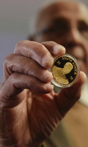 Ex-preso político Ahmed Kathrada segura uma moeda de ouro 24 quilates em homenagem ao ex-presidente Nelson Mandela, em Pretoria