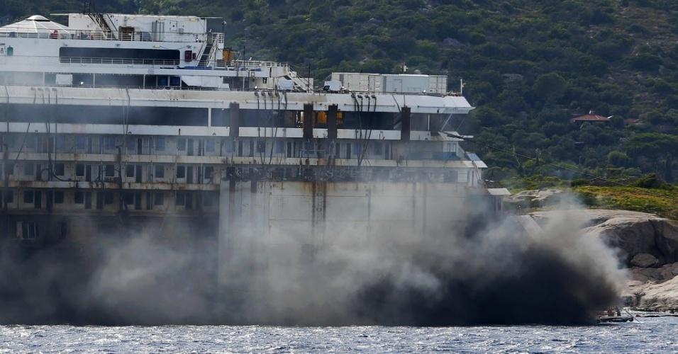 22.jul.2014 - Fumaça preta sai da parte de trás do navio Costa Concordia durante a operação para desencalhá-lo na Ilha de Giglio, na Itália