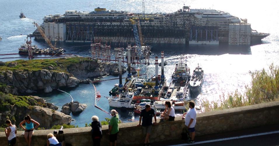 23.jul.2014 - O navio Costa Concordia é observado nesta durante operação para retirá-lo da ilha de Giglio, na Itália, onde naufragou há mais de dois anos matando 32 pessoas