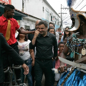 25.jul.2014 - O candidato do PSDB à presidência da República, Aécio Neves, caminha em rua da favela Vigário Geral, na zona norte do Rio de Janeiro