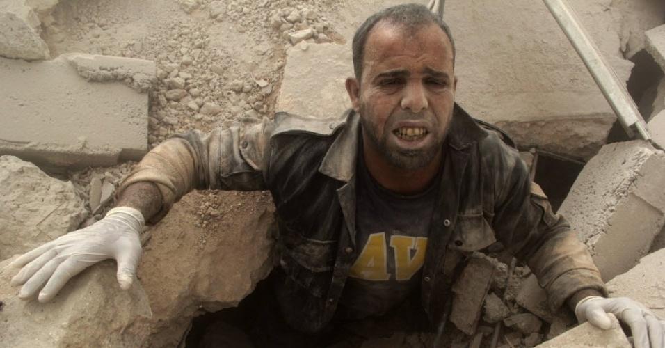 27.jul.2014 - Um membro da defesa civil fica preso sob escombros em local atingido por bombas no bairro de Al-Shaar, em Aleppo, Síria