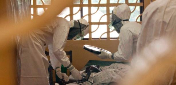 Médicos cuidam de paciente com ebola em hospital de Monrovia, na Libéria