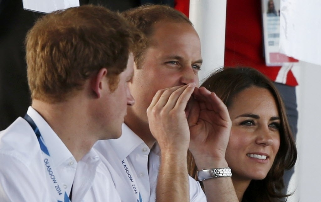28.jul.2014 - O príncipe britânico William, entre o príncipe Harry e Kate Middleton, grita durante partida de hockey dos Jogos da Commonwealth 2014, em Glasgow, na Escócia