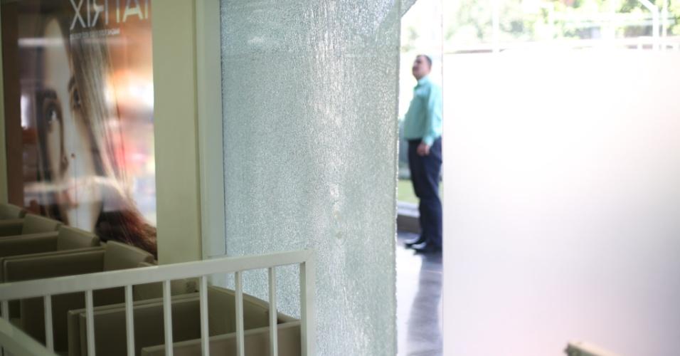 4.ago.2014 - Homem observa porta de vidro atingida por bala durante tiroteio na altura do número 2.000 da avenida Faria Lima, no Jardim Paulistano, zona oeste de São Paulo. Pelo menos quatro pessoas ficaram feriadas