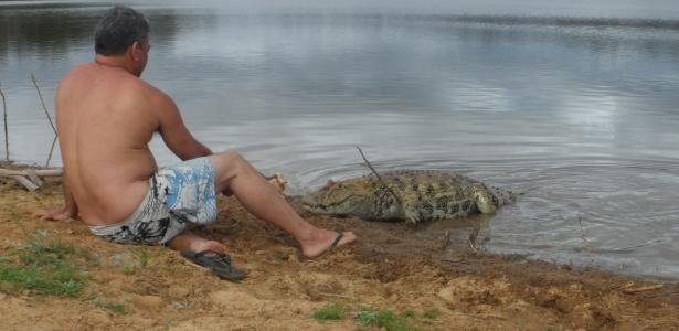 """O agricultor Elias da Silva oferece comida ao seu """"amigo jacaré"""" às margens de uma barragem em Maetinga, cidade do sertão da Bahia"""