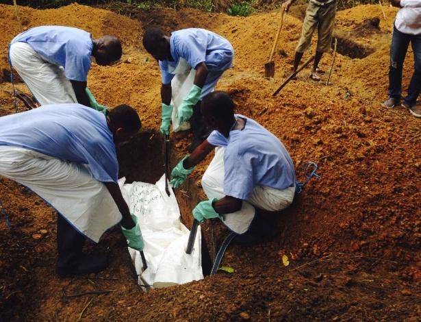 Voluntários baixam um corpo que foi preparado dentro das práticas de sepultamento seguro para evitar o risco de contágio de ebola, em uma sepultura em Kailahun, em Serra Leoa, nesta terça-feira (5)