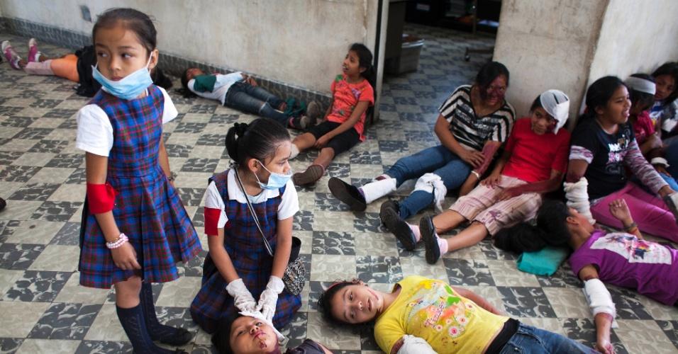 07.ago.2014 - Estudantes da escola Jose Joaquin Palma, na Guatemala, fazem simulação de terremoto. O treinamento foi realizado em 28 escolas primárias na área metropolitana da cidade.