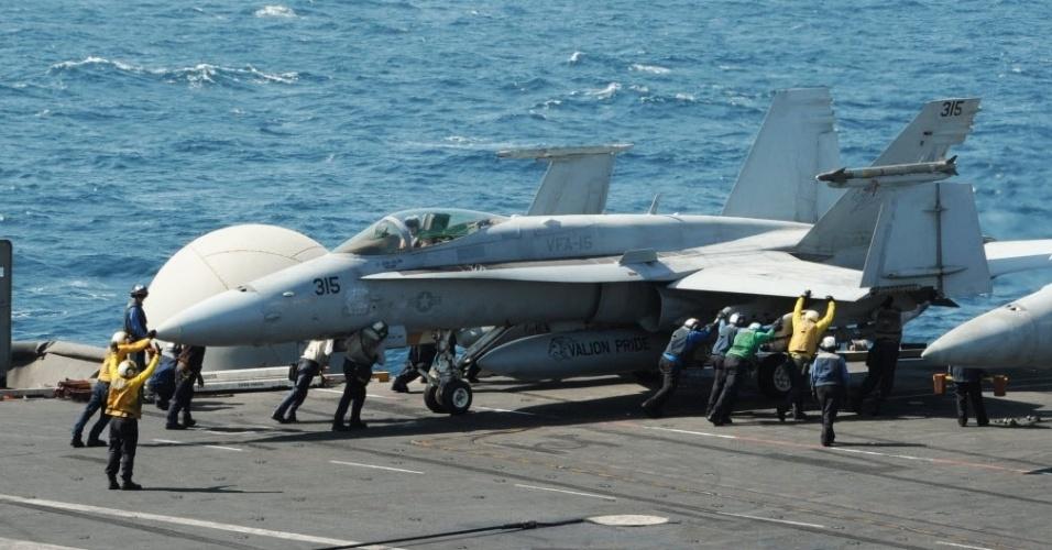 8.ago.2014 - Caça norte-americano é manobrado no porta-aviões George H.W. Bush no Golfo Pérsico, durante operações militares no Iraque, nesta sexta-feira (8). Agência Federal de Aviação (FAA) dos EUA proibiu que aviões comerciais americanos sobrevoem o Iraque, onde o Exército americano está realizando os seus primeiros ataques aéreos contra os jihadistas do Estado Islâmico (EI)