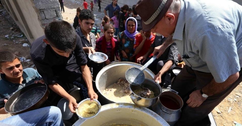 9.ago.2014 - Famílias iraquianas da minoria étnica yazidi, que fugiram da violência na cidade de Sinjar, no norte do Iraque, recebem comida em abrigo na cidade de Dohuk, na região autônoma curda do país